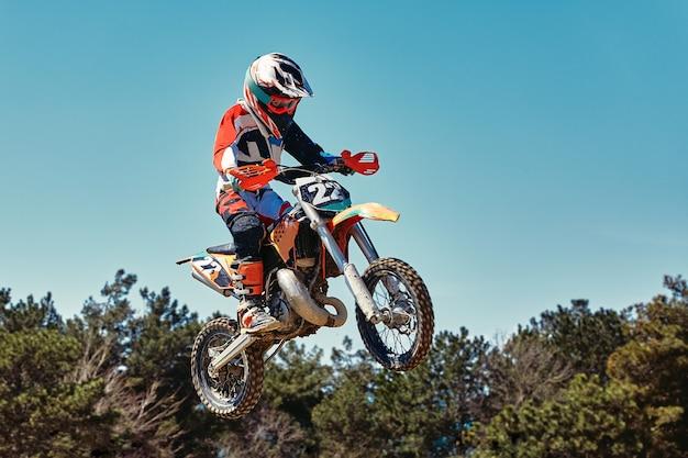 Extreme concept daag jezelf uit extreme sprong op een motorfiets op een achtergrond van blauwe lucht met wolken kopieer de ruimte alles of niets