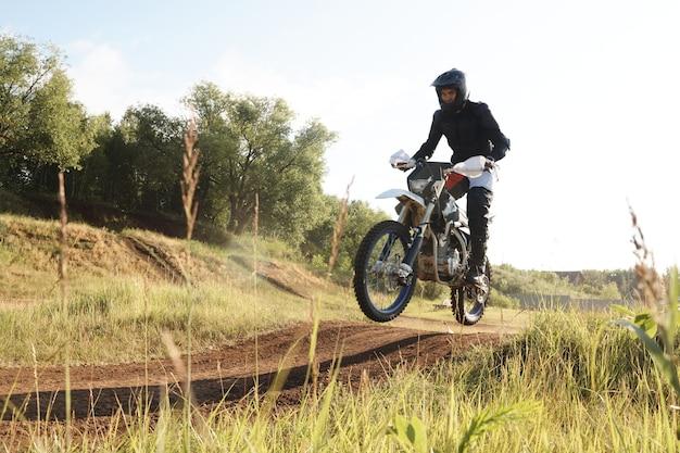 Extreme man in beschermende kleding die in de lucht is tijdens het motorrijden op heuvels bij competitie