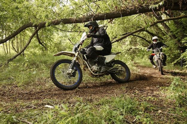 Extreme mannen in helmen die motorfietsen rijden op een ruwe weg die boshindernissen overwinnen