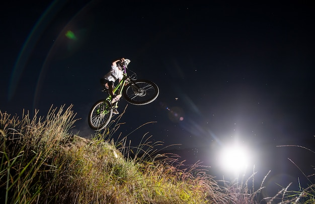 Extreme ruiter die hoogspringen op een bergfiets maakt van de helling tegen nachthemel