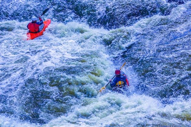 Extreme wildwatervaren trip. een groep mensen (team) in kajaks oefenen het oversteken van de stroomversnellingen. kayaker peddelen op de bergrivier. kajakken concept.