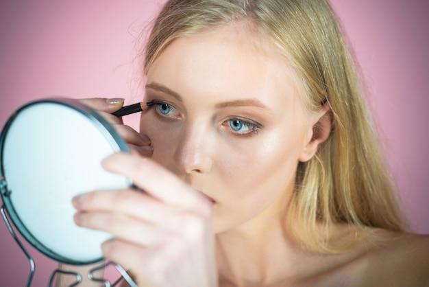 Eyeliner make-up aantrekkelijke blonde vrouw make-up sexy meisje aanbrengend potlood voor ogen ziet er in