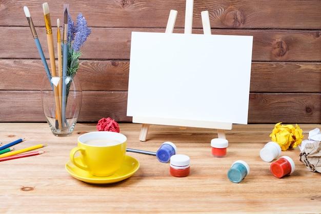 Ezel, kunstborstels, verf en koffie op houten achtergrond