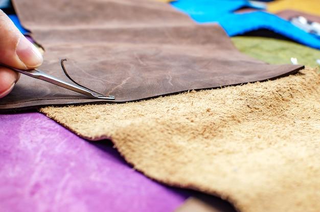Fabricageproces van lederwaren. gereedschap voor het naaien van tassen, portefeuilles, koppelingen. gekleurde stukken leer. detailopname