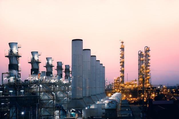 Fabriek van olie en gasraffinaderijbedrijf met de achtergrond van de zonsopganghemel, de petrochemische industrie, rookstapels van elektrische centrale