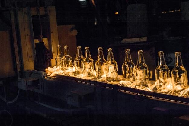 Fabriek voor de productie van glazen flessen. glazen flessen op een transportband met vuur