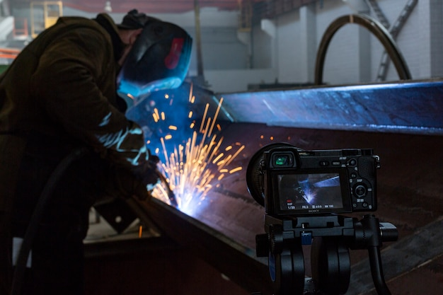 Fabrieksarbeider bij de vonken van de de close-upfilm van het fabriekslassen