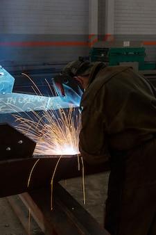 Fabrieksarbeider bij de vonken van de het lassenclose-up van de metaal industriële fabriek