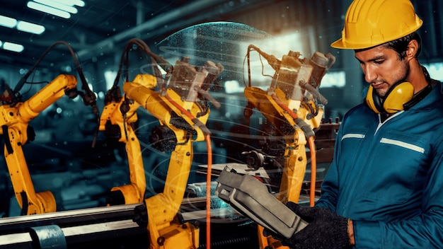 Fabrieksarbeider controleert robotarm in fabriek