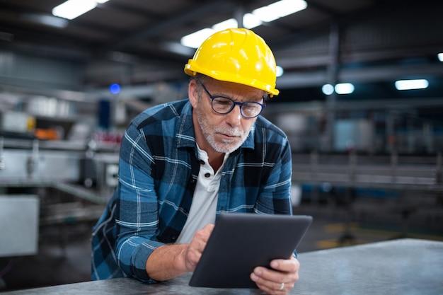 Fabrieksarbeider die digitale tablet in de fabriek gebruiken
