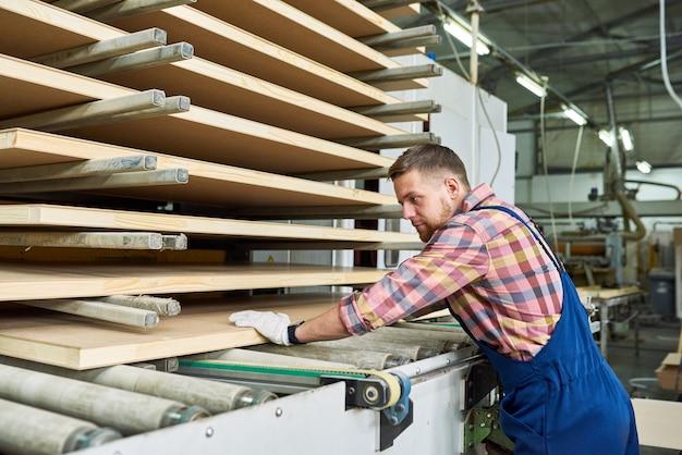 Fabrieksarbeider die hout in workshop stapelen