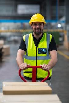 Fabrieksarbeider die karretje van kartondozen trekt
