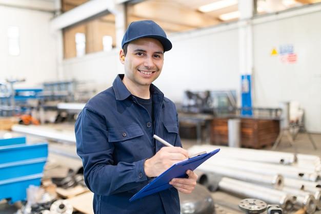 Fabrieksarbeider die op een document schrijft