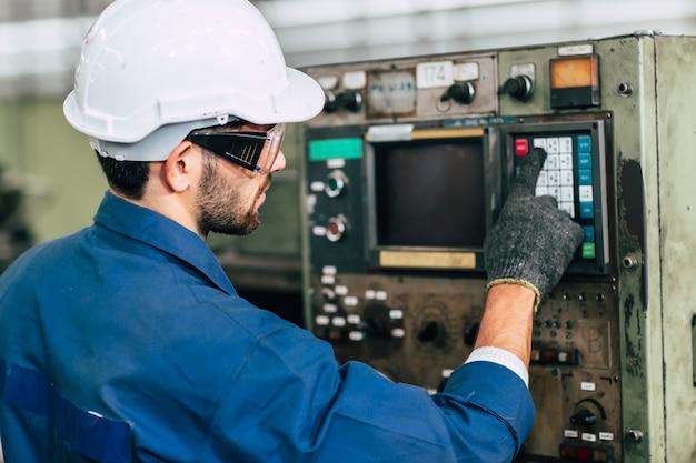 Fabrieksarbeider man bedient de machine, hooggeschoolde arbeidsindustrie met veiligheidskleding.