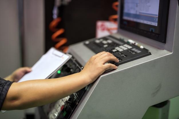 Fabrieksarbeider op toetsenbord om machine te bevelen