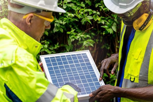 Fabrieksarbeider technicus ingenieur mannen controleren zonnecelpaneel voor duurzame technologie