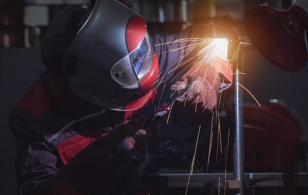Fabrieksarbeiderarbeider bij de staalstructuur van de fabriekslassen