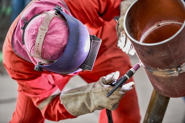 Fabrieksarbeiderarbeider bij de staalstructuur van het fabriekslassen