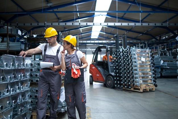 Fabrieksarbeiders controleren kwaliteit van producten in industrieel magazijn