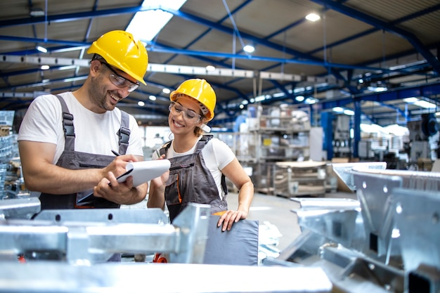 Fabrieksarbeiders die de kwaliteit van producten in grote industriële hal controleren