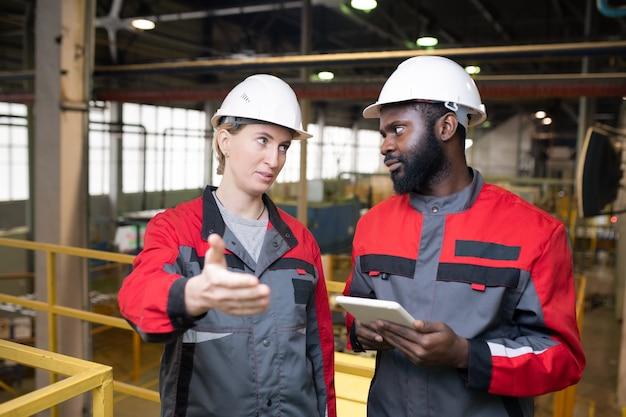 Fabrieksarbeiders die iets bespreken