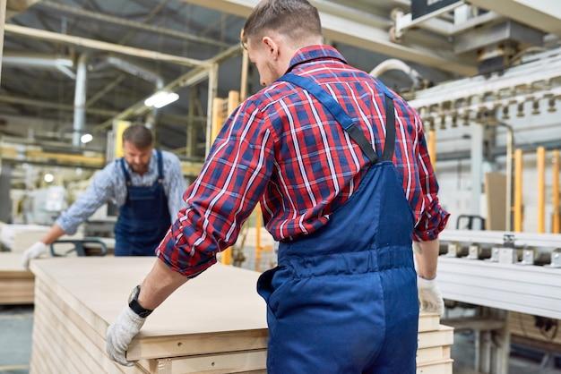 Fabrieksarbeiders die materialen verplaatsen