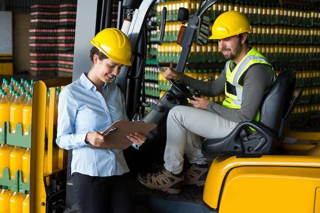 Fabrieksarbeiders die verslag controleren op klembord in fabriek