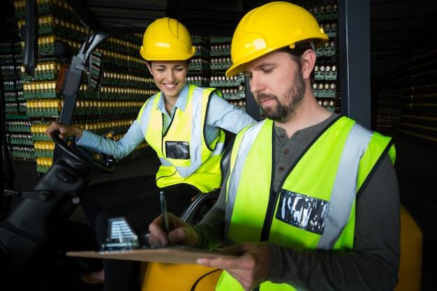 Fabrieksarbeiders die verslag op klembord in fabriek onderhouden