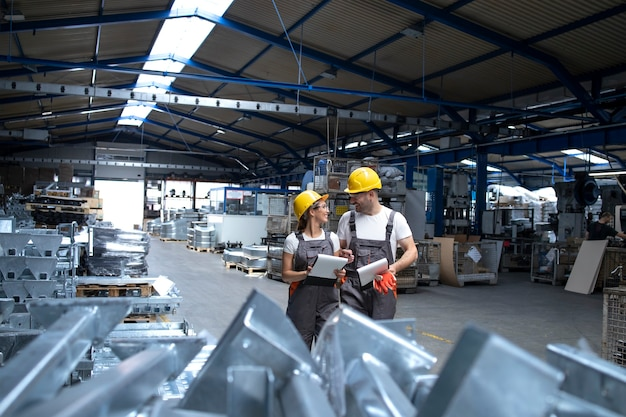Fabrieksarbeiders in industriële productiehal die ideeën uitwisselen