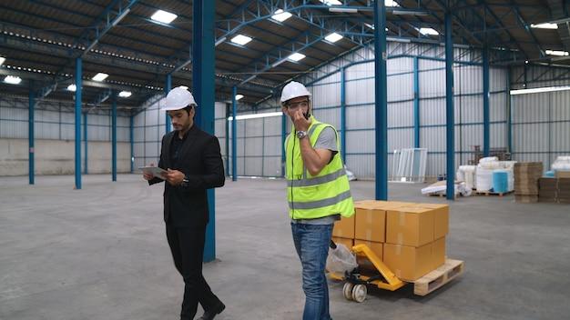 Fabrieksarbeiders leveren dozenpakket op een duwwagen in het magazijn. industrie supply chain management concept.