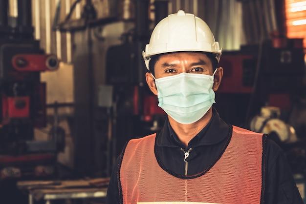 Fabrieksarbeiders met gezichtsmasker beschermen tegen uitbraak van coronavirus covid-19