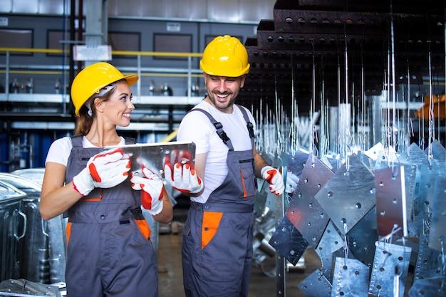 Fabrieksarbeiders werken samen in industriële metalen productielijn