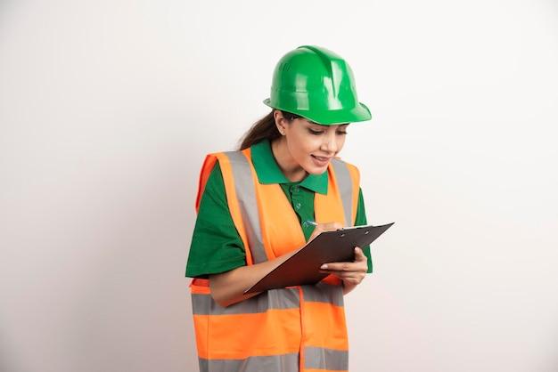 Fabrieksarbeidervrouw met potlood en klembord. hoge kwaliteit foto