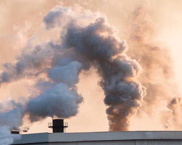 Fabrieksbrandend riet met rook en verontreiniging op hemel, het globale verwarmen