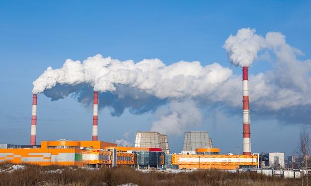 Fabriekshoofdleidingen die veel rook in de atmosfeer uitstoten. de blauwe lucht wordt verduisterd door rook uit fabrieksschoorstenen
