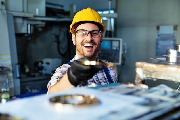 Fabrieksingenieur controleert de kwaliteit van het vervaardigde onderdeel