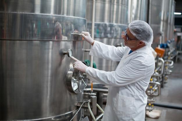 Fabrieksingenieur die een manometer van opslagtank controleert