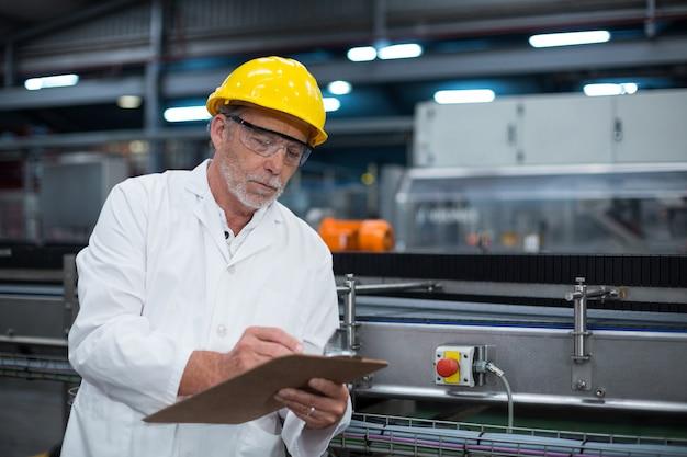 Fabrieksingenieur die verslag op klembord bijhoudt