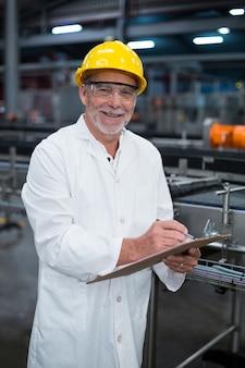 Fabrieksingenieur die verslag op klembord in fabriek onderhouden