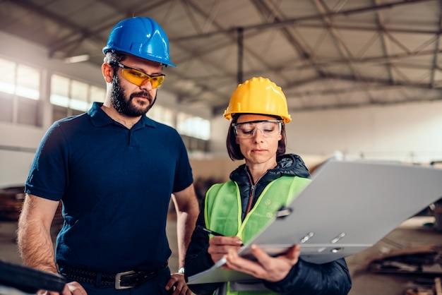 Fabrieksleider die productieschema controleert op cnc-machine