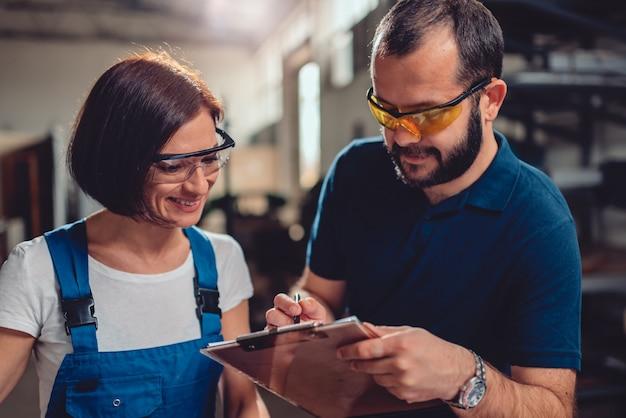 Fabrieksleider die werkorder voor vrouwelijke arbeider controleert