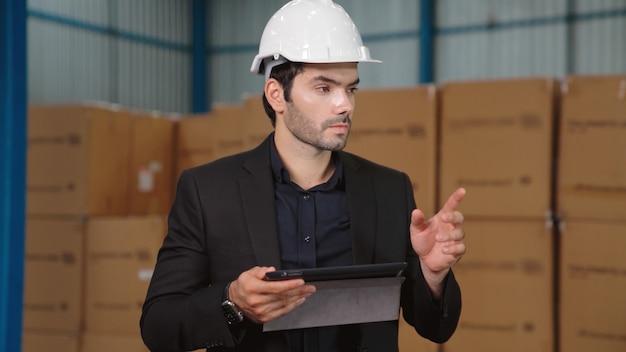 Fabrieksmanager met behulp van tabletcomputer in magazijn of fabriek. industrie en supply chain management concept.