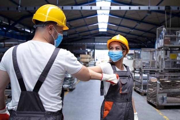 Fabrieksmedewerkers begroeten elkaar met elleboogstoten vanwege wereldwijde pandemie van het coronavirus en infectiegevaar