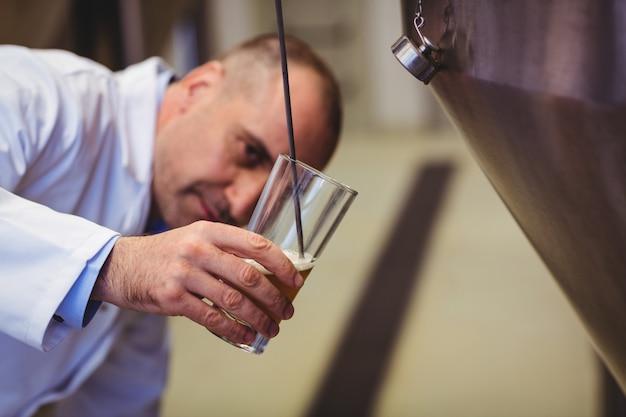 Fabrikant bier vullen in glas bij brouwerij