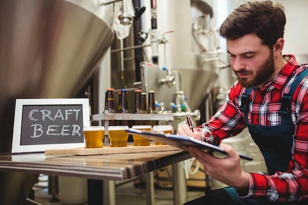 Fabrikant schrijven op blocnote in brouwerij