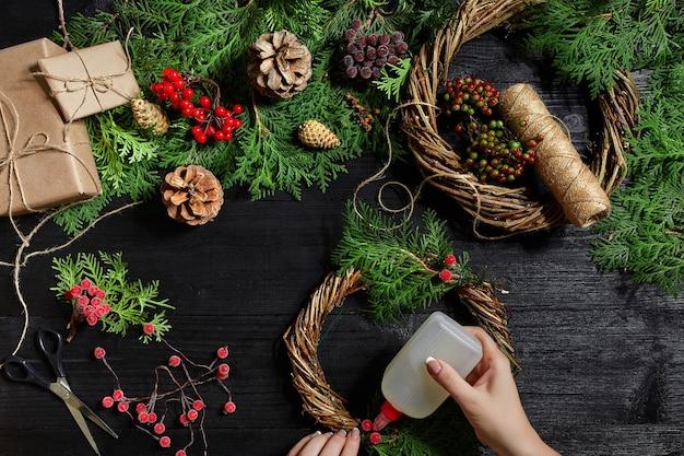 Fabrikant van kerstdecor met hun eigen handen kerstkrans voor de vakantie het nieuwe jaar c...