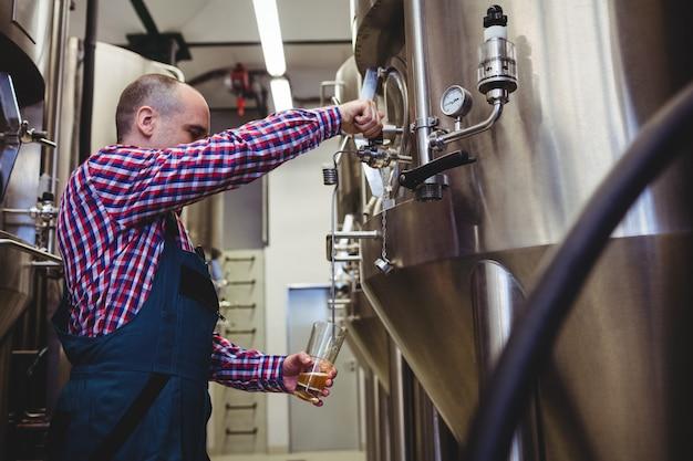 Fabrikant vullen bier uit opslagtank bij brouwerij