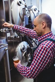 Fabrikant vullen bier uit opslagtank bij distilleerderij