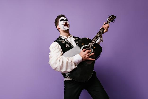 Face art man stelt zichzelf voor als rockmuzikant en poseert emotioneel met gitaar. binnenportret van de mens op lila muur.