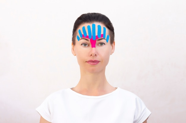 Face taping, close-up van het gezicht van een meisje met cosmetologische anti-rimpel tape. gezicht esthetische taping. niet-invasieve anti-aging liftmethode voor het verminderen van rimpels